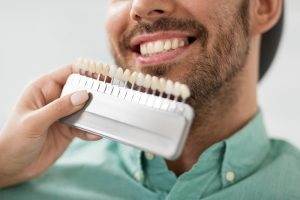 Porcelain veneers compared to a man with stubble and a teal shirt's teeth.