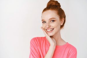 A young woman with red hair and a pink shirt rests her head on her hand and smiles, showing off her porcelain veneers.