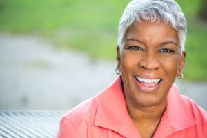 An older African American woman with short, white hair, wearing a salmon shirt sits outside and smiles, showing off her porcelain veneers.