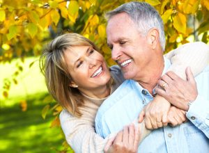 A couple hugs in front of a tree after their cosmetic dentistry procedures.