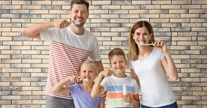 A family smiles with their toothbrushes after their family dentistry appointment.