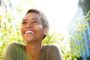 A young woman with short, curly hair looks toward the sky and smiles to show off her teeth whitening results.