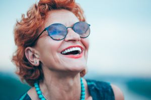 An elderly woman with red hair and sunglasses smiles, showing off her dentures.